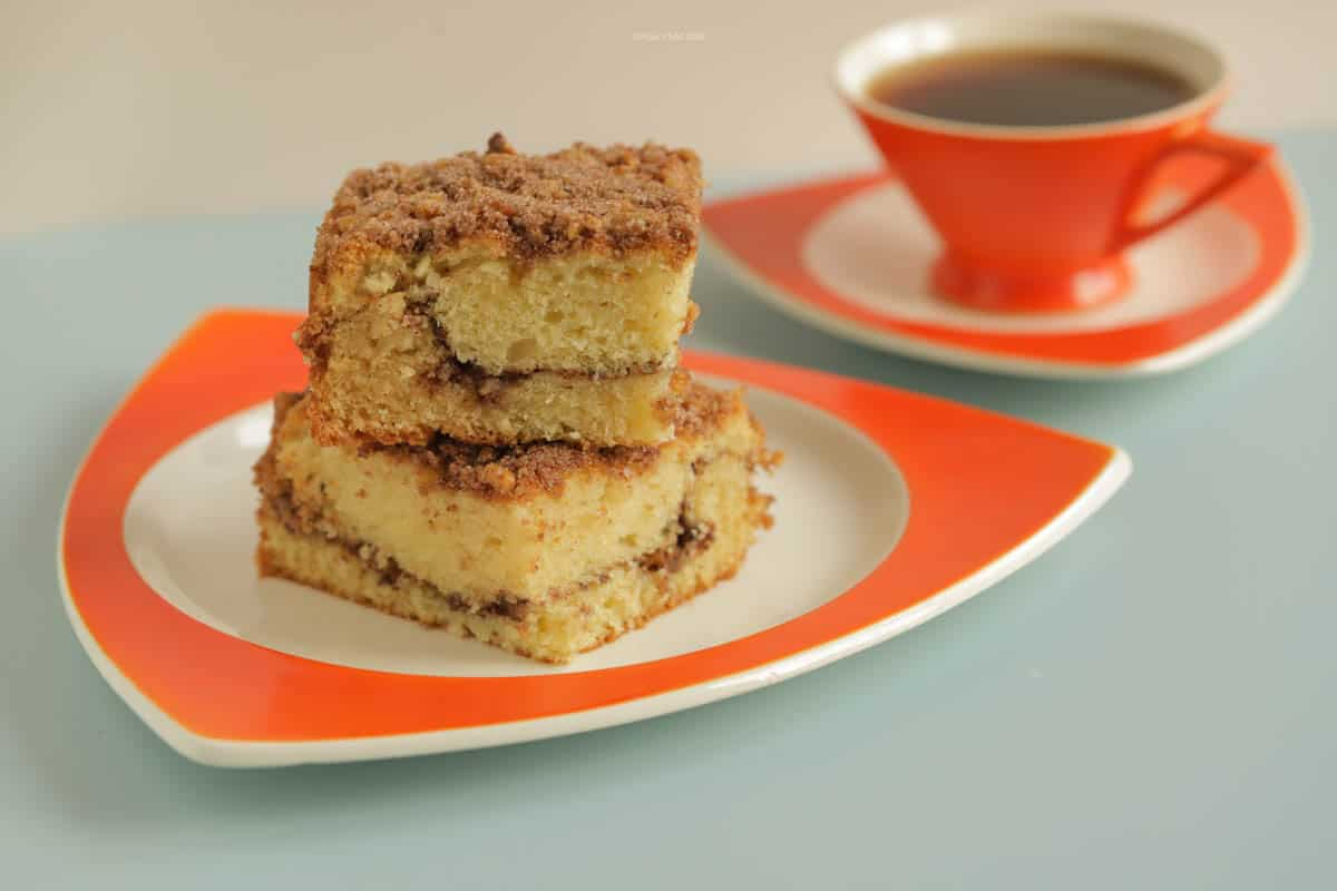 Two pieces of coffee cake stacked on a plate next to a hot cup of coffee