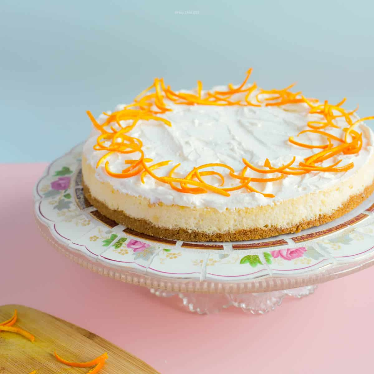 This atomic orange cheesecake with whipped cream topping is decorated with peeled orange zest around the outer rim