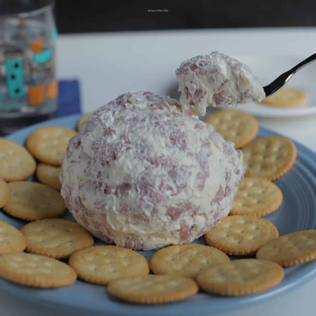 Chipped beef and cream cheese ball appetizer on a party platter with crackers.
