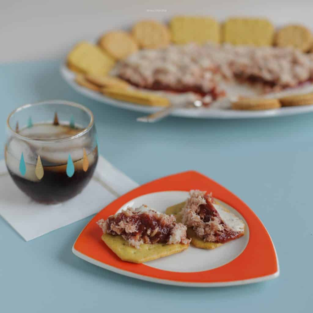 A mid century setting with crab dip on a flame red tricorne plate.