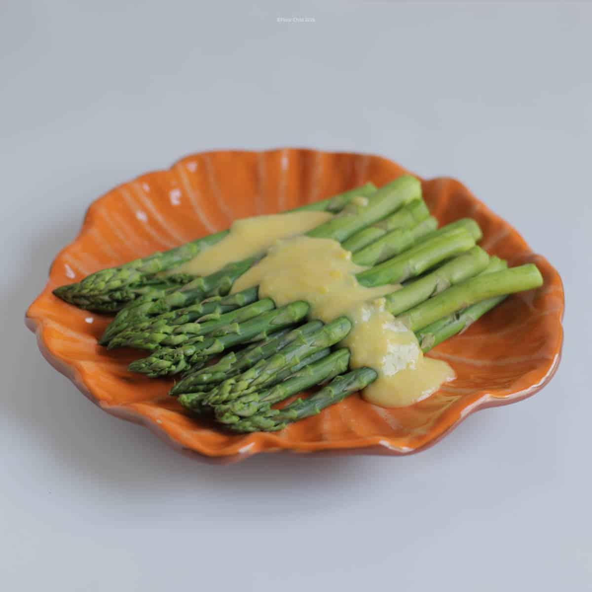Hollandaise Sauce poured over an asparagus side dish