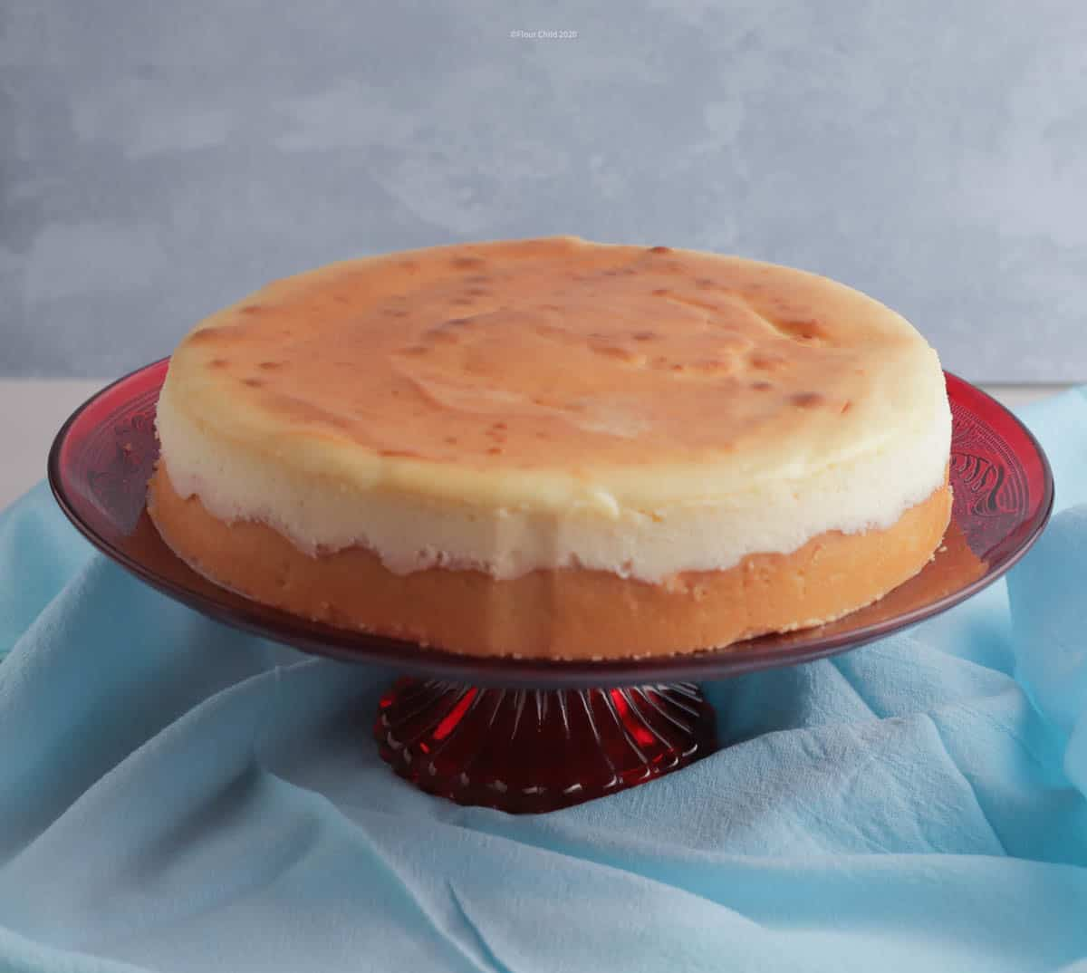 New York style cheesecake on a red pedestal cake stand