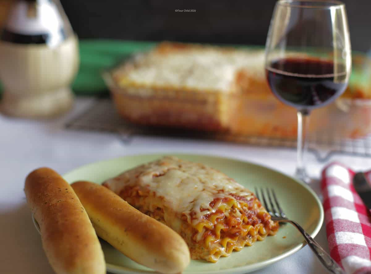 Lasagna on a plate with two breadsticks and a fork, a glass of red wine next to the plate