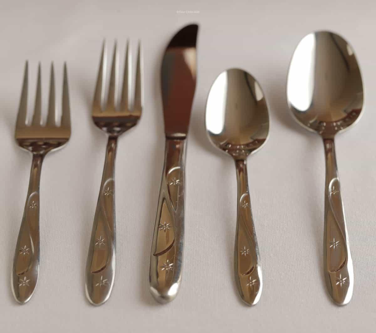 Tablespoon, teaspoon, knife, dinner fork and salad fork in Americana Star flatware pattern