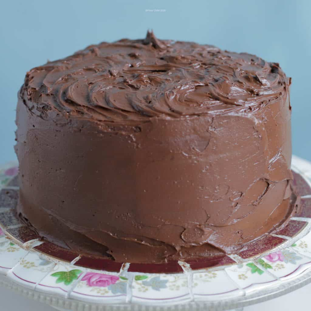 Close up photo of chocolate cake covered in chocolate buttercream frosting