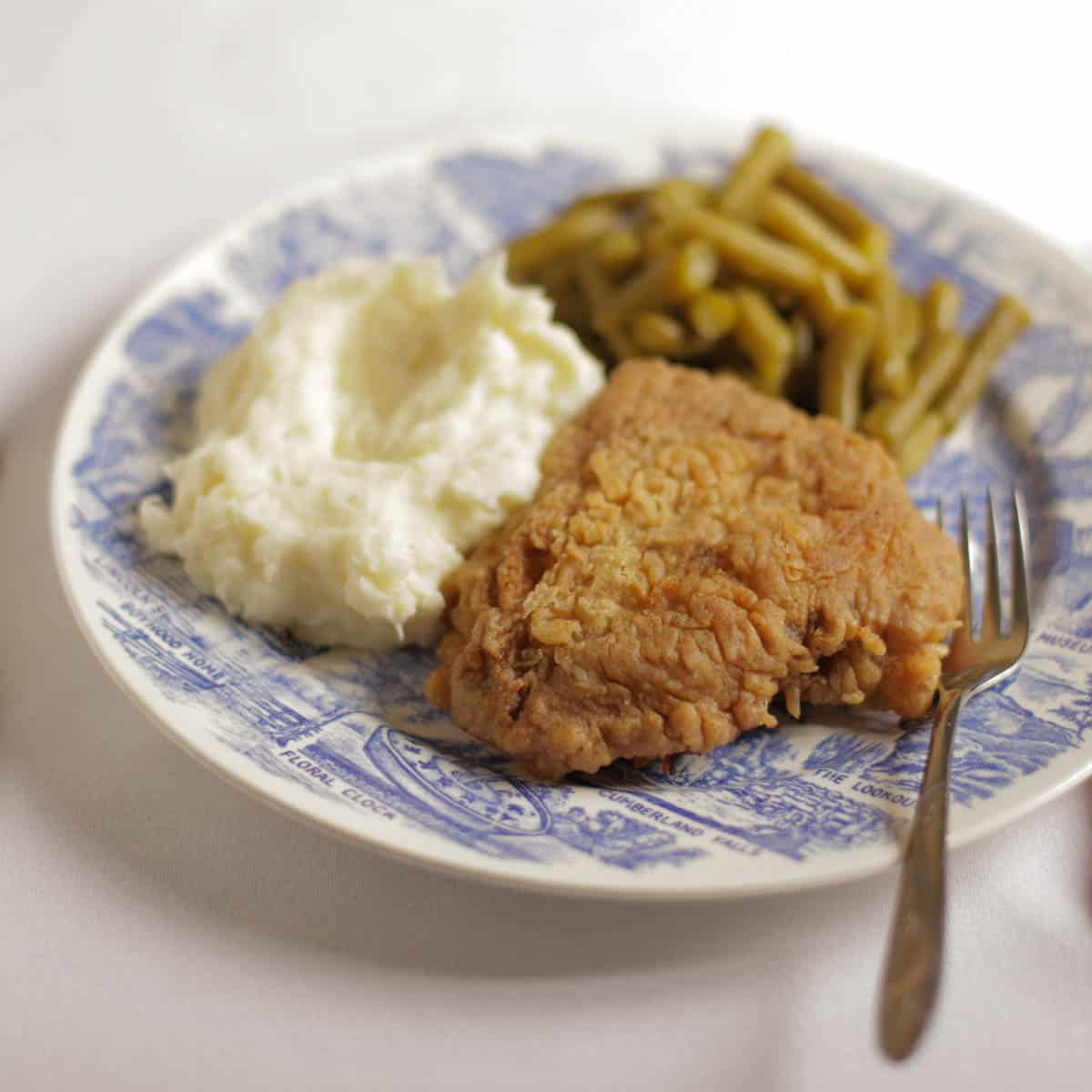 Chicken fried steak on a plate next to mashed potatoes and green beans.