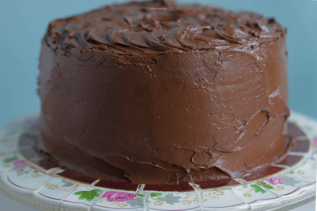 Chocolate cake covered with chocolate buttercream frosting sitting on a round cake platter