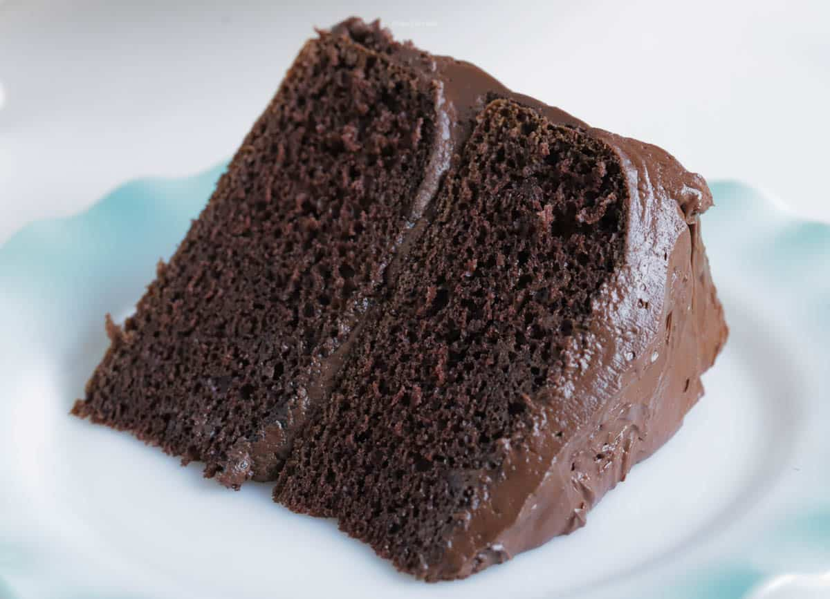 A slice of chocolate cake on a plate covered in chocolate buttercream frosting