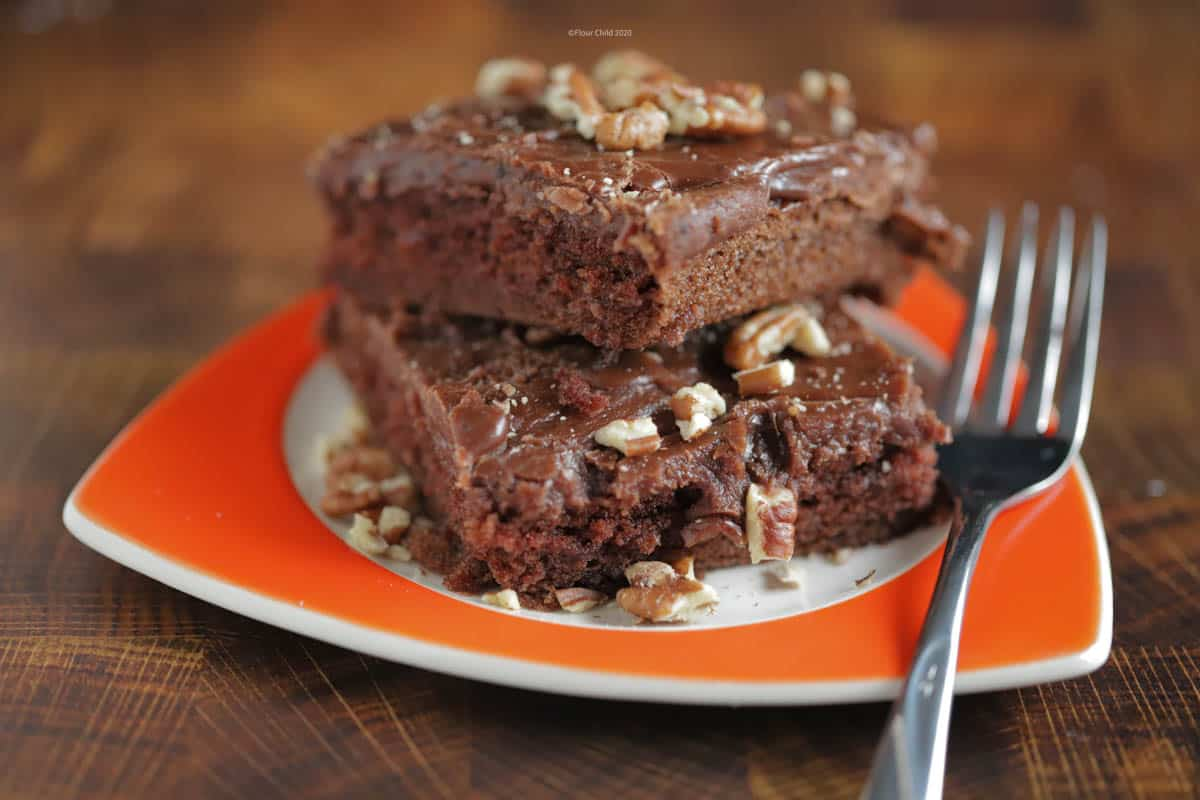 Two brownies with nuts on top sitting on an orange plate with a fork next to it
