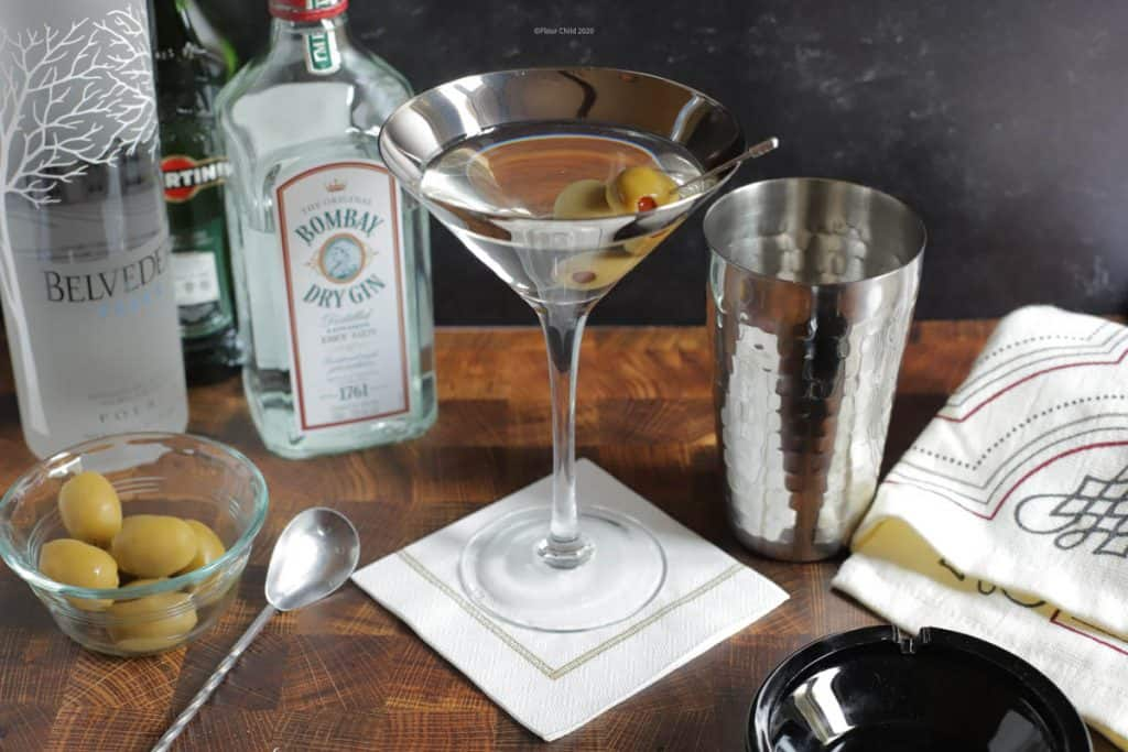 Martini cocktail bar set in a glass with olives and vodka or gin bottles.