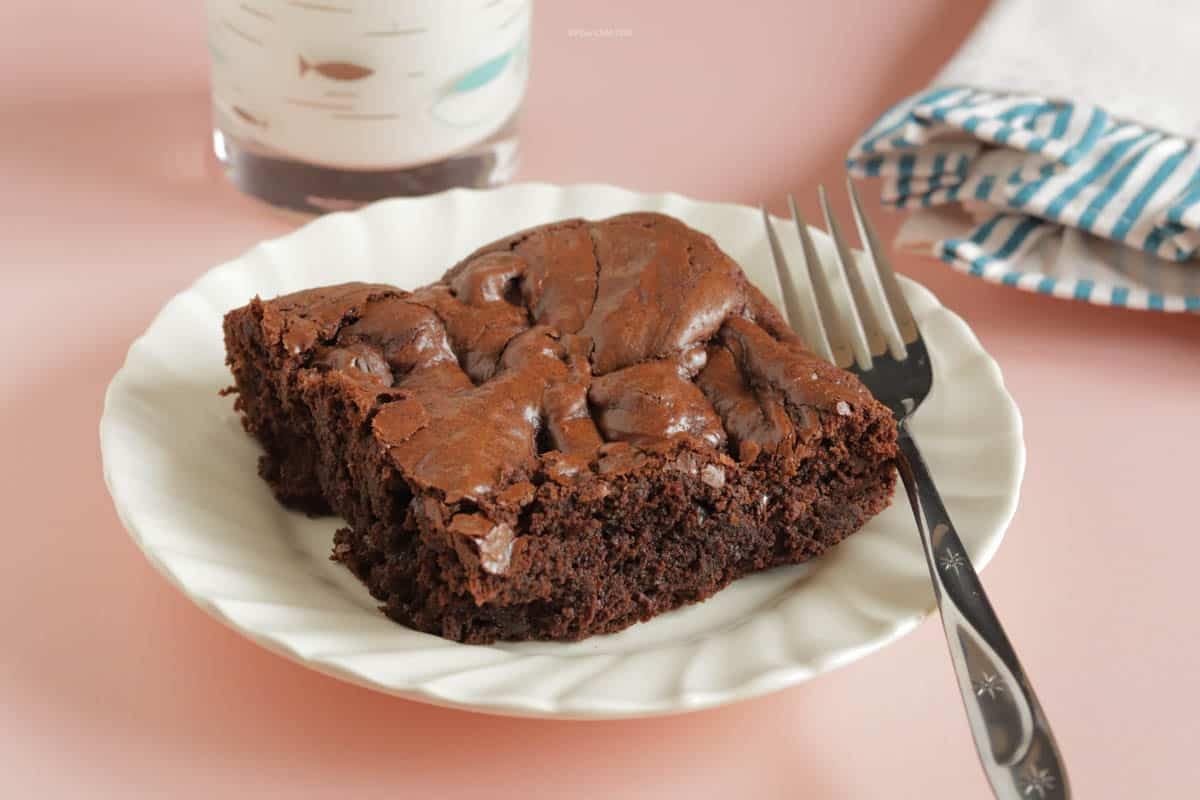 30 Minute Fast and Easy Brownies on a white plate with a fork. Glass of milk and napkin next to the plate.