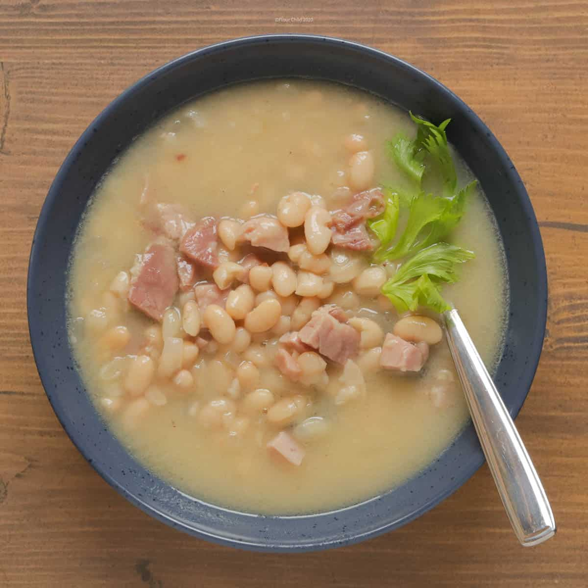 Traditional Navy Bean Soup in a blue bowl with spoon.