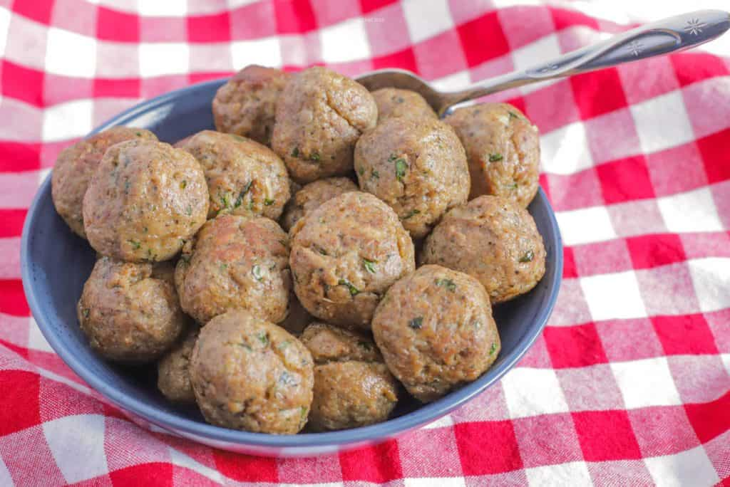 Two dozen meatballs piled into a blue bowl on top of a red checkerboard tablecloth