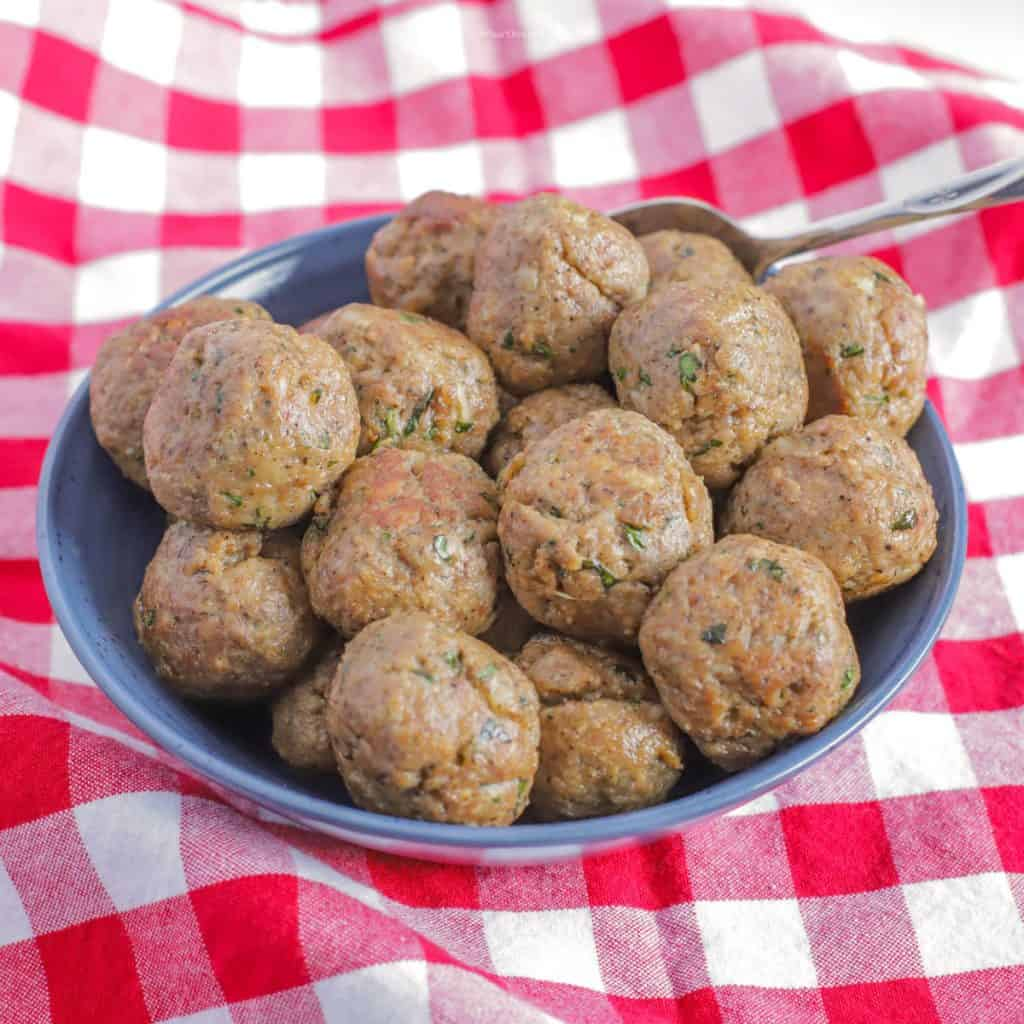 Meatballs piled into a blue bowl on top of a red checkered tablecloth