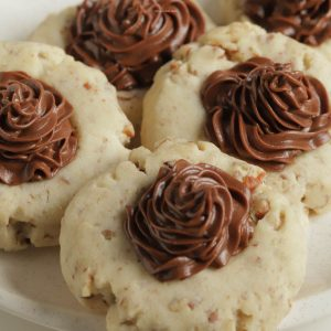Four chocolate frosted pecan sandies cookies on a plate