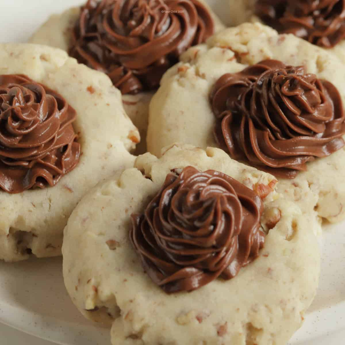 Three chocolate frosted pecan cookies on a plate