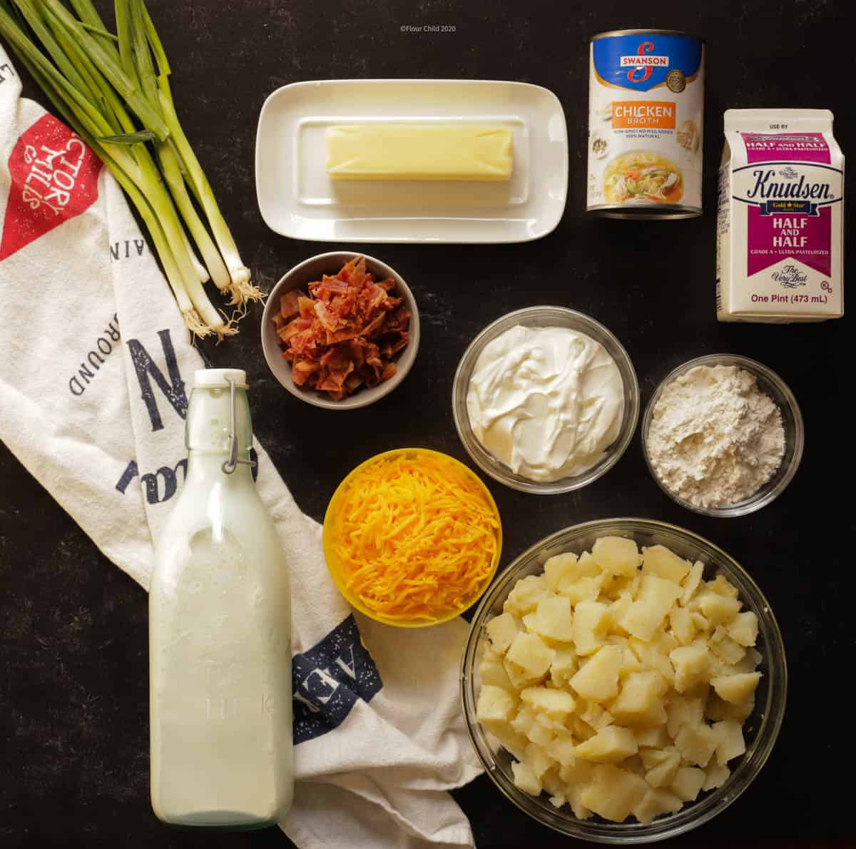 All of the ingredients needed to make baked potato soup are set out on a table
