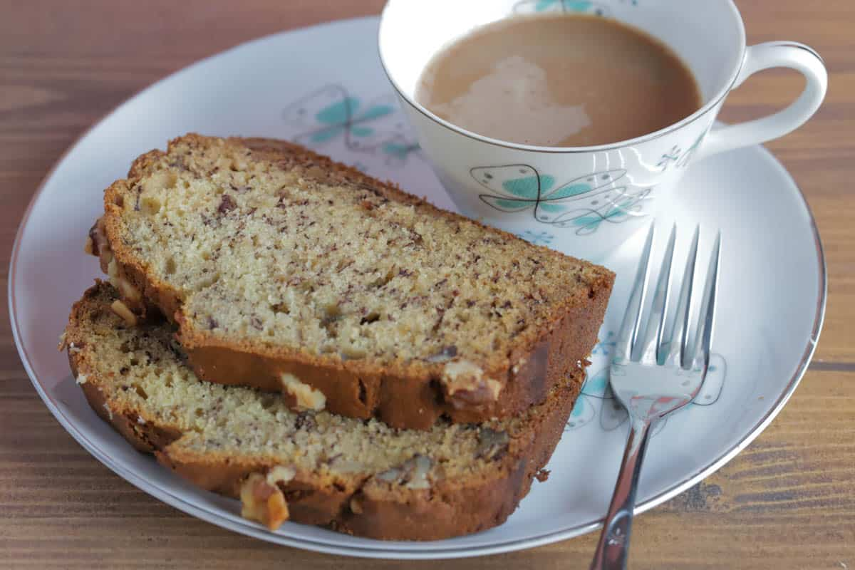 Two slices of banana walnut bread on a plate, with a fork and a cup of coffee next to it.