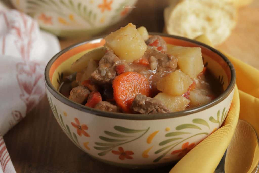 A big bowl of beef burgundy stew piled high with chunks of beef, potatoes, peas & carrots