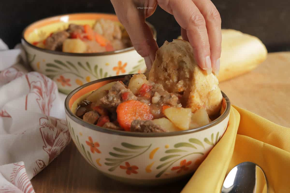 A bowl of beef burgundy stew with chunks of meat, potatoes, and vegetables piled high. A hand is dipping a piece of French bread into the stew.