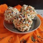 Three popcorn balls in a bowl with orange, green, black and purple candy sprinkles over them