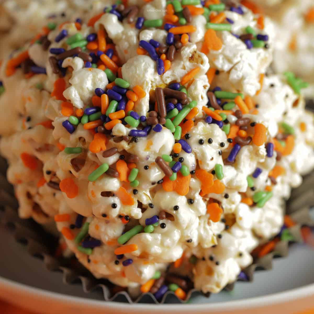 A close up image of a popcorn ball with Halloween colored sprinkles on it in black, orange, green and purple