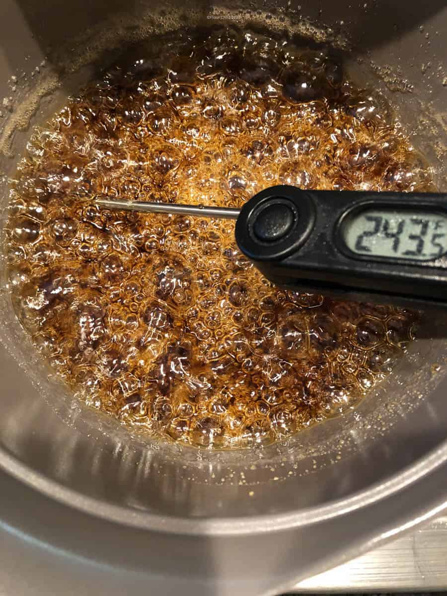 Candy thermometer inserted into boiling syrup