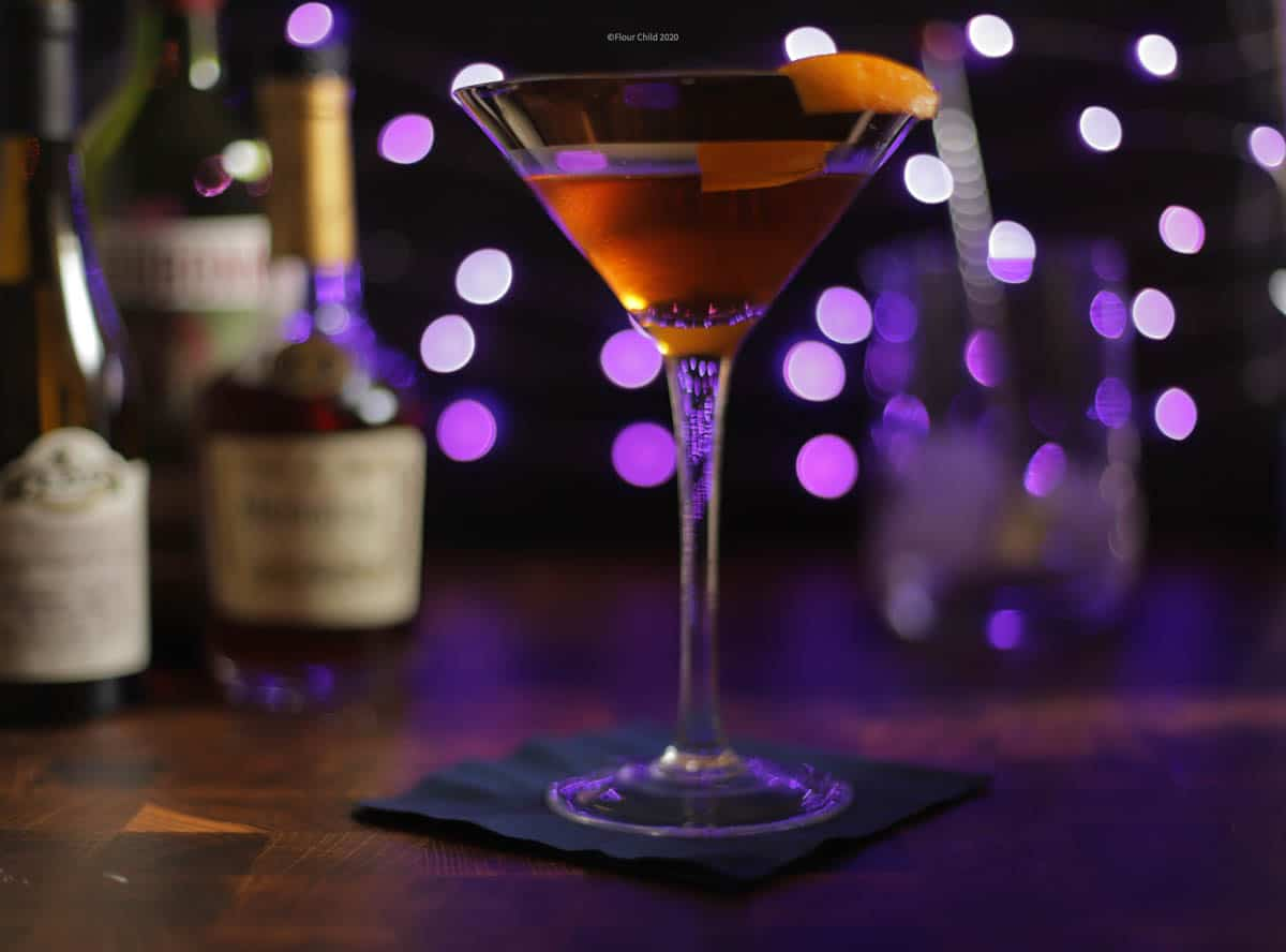 Corpse Reviver cocktail in a cocktail glass with an orange twist on a purple background.