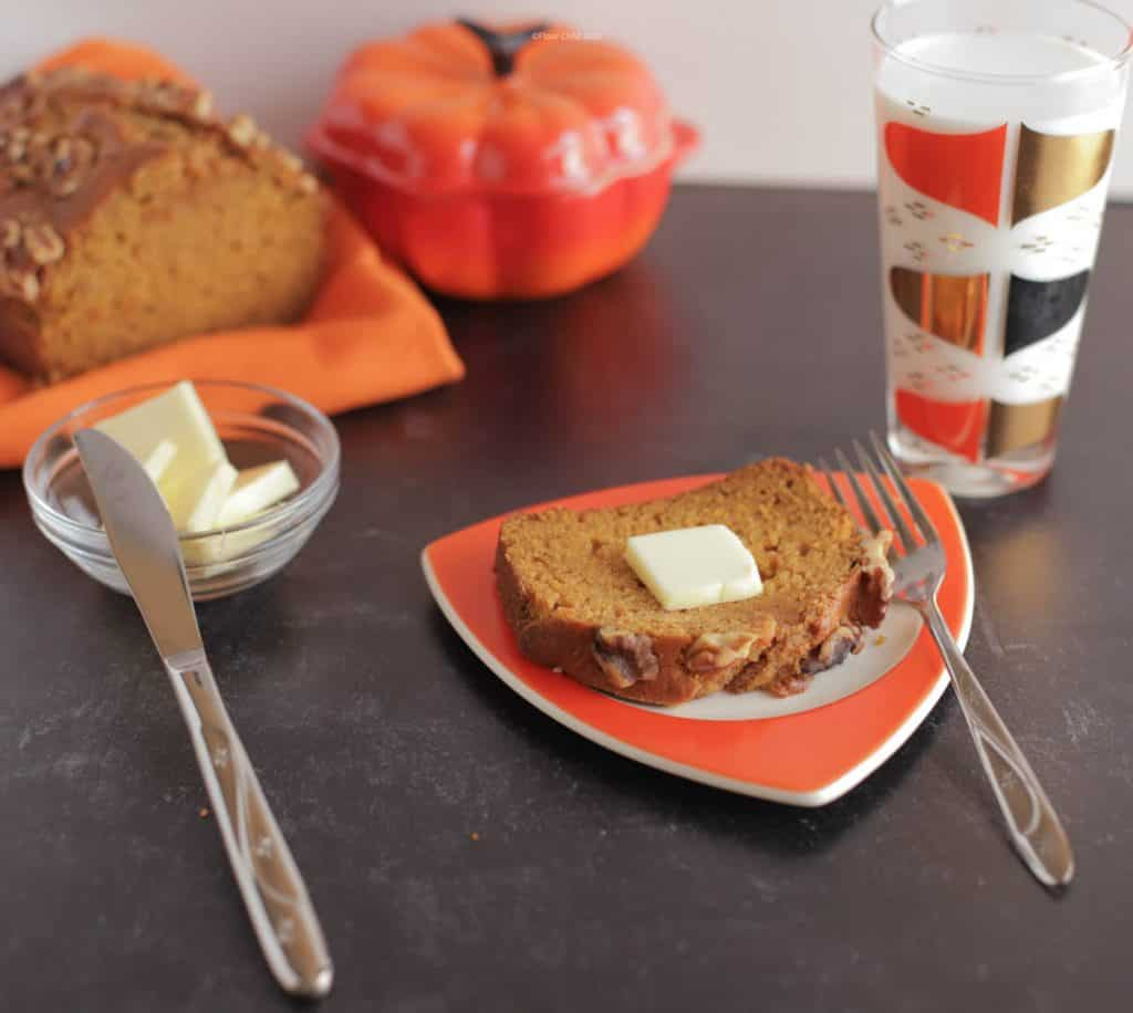 A slice of pumpkin bread with a pat of butter on top, sitting on an orange plate next to a glass of milk.