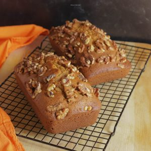 Two loaves of pumpkin bread on a cooling rack