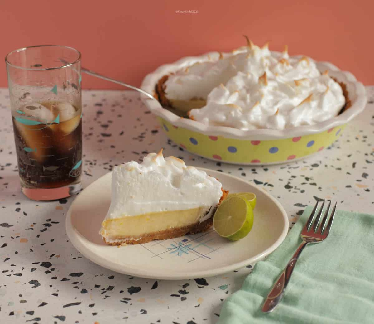 A lice of key lime pie on a plate with a lime wedge next to it. Pie dish in the background and a glass of coke and a fork next to the plate.