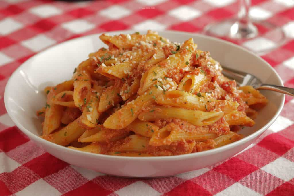 A while bowl with penne pasta in vodka sauce piled high inside