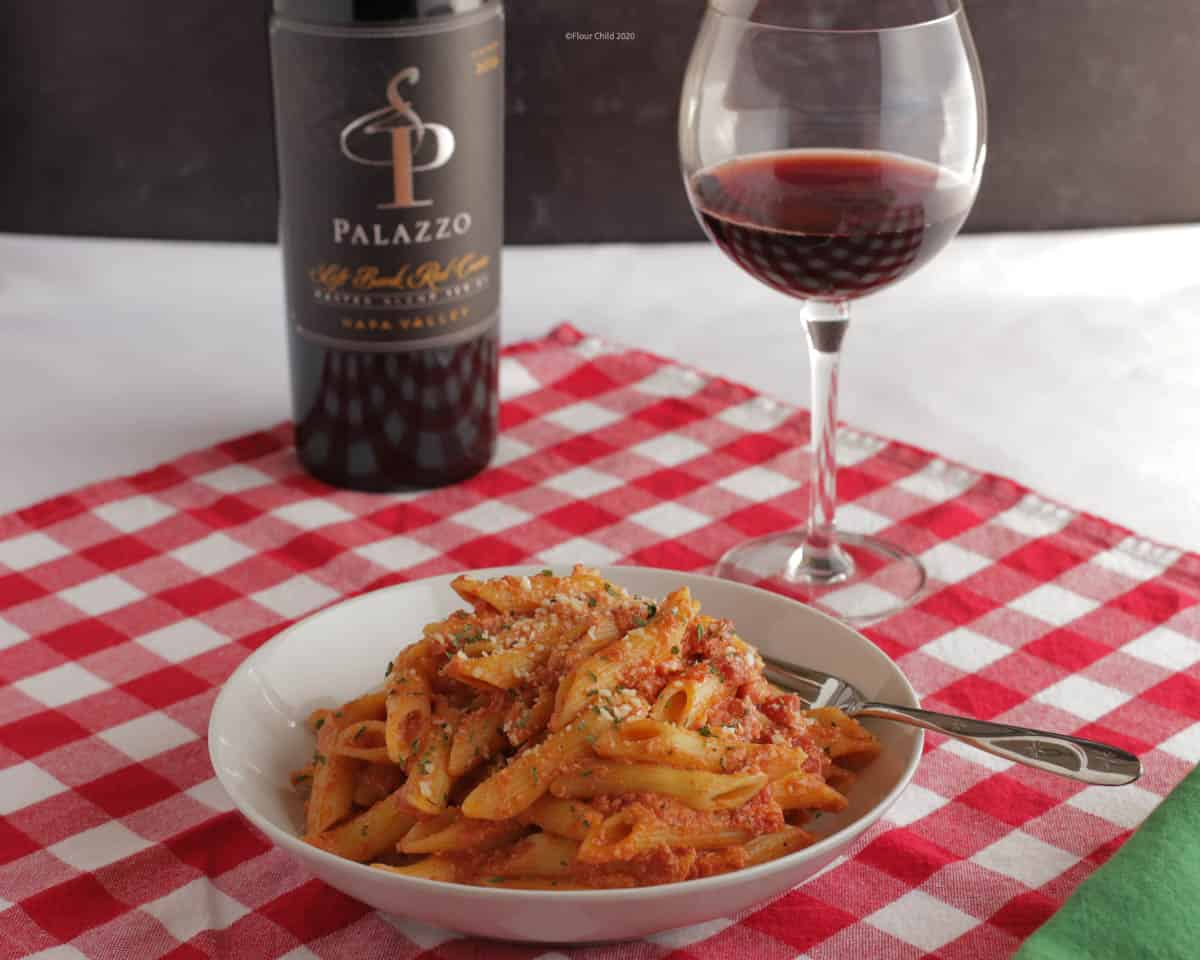 Penne pasta in vodka sauce in a white bowl with a fork, a bottle of wine and a glass of wine in the background