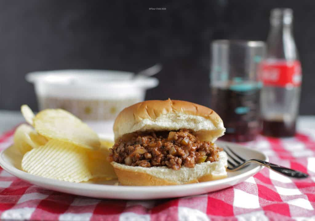 Sloppy Joe on a bun, sitting on a plate with potato chips and a fork