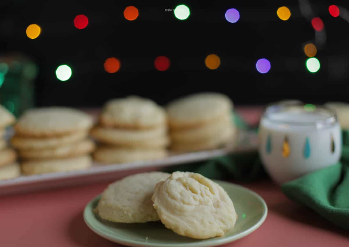 Two butter cookies on a green plate, with a tray of butter cookies behind it.