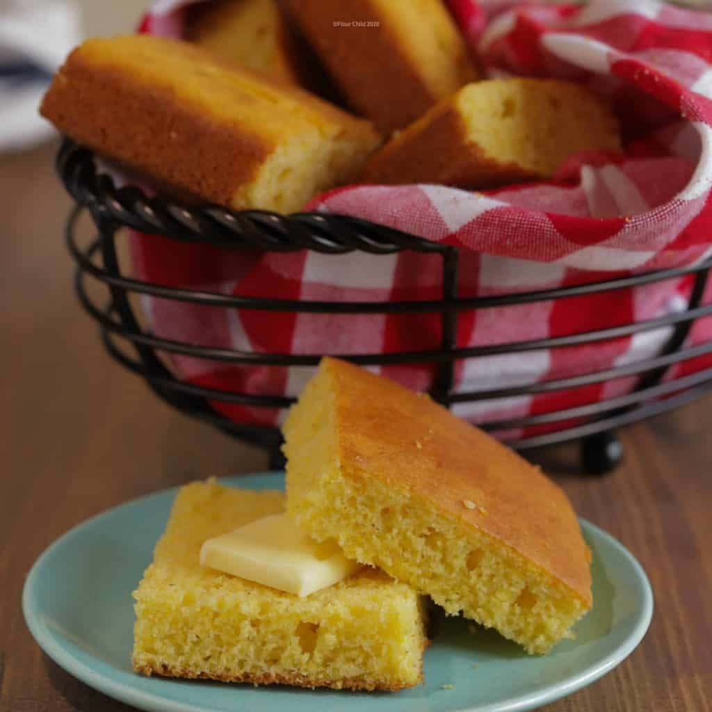 A piece of cornbread sliced in half on a small blue bread plate, with a pat of butter on one piece. A basket of cornbread is in the background.