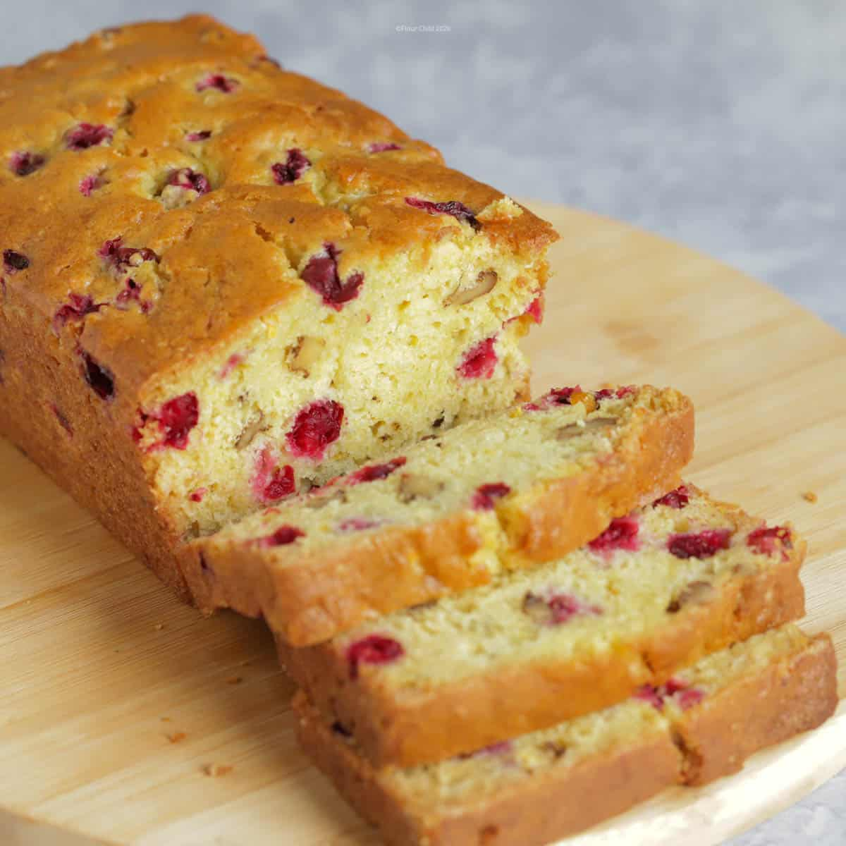 A loaf of cranberry orange quick bread on a cutting board with 3 slices cut off