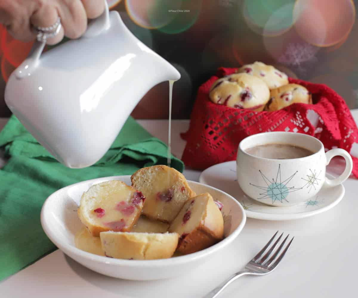 Dish of cranberry muffins with hot butter sauce being poured over the top.