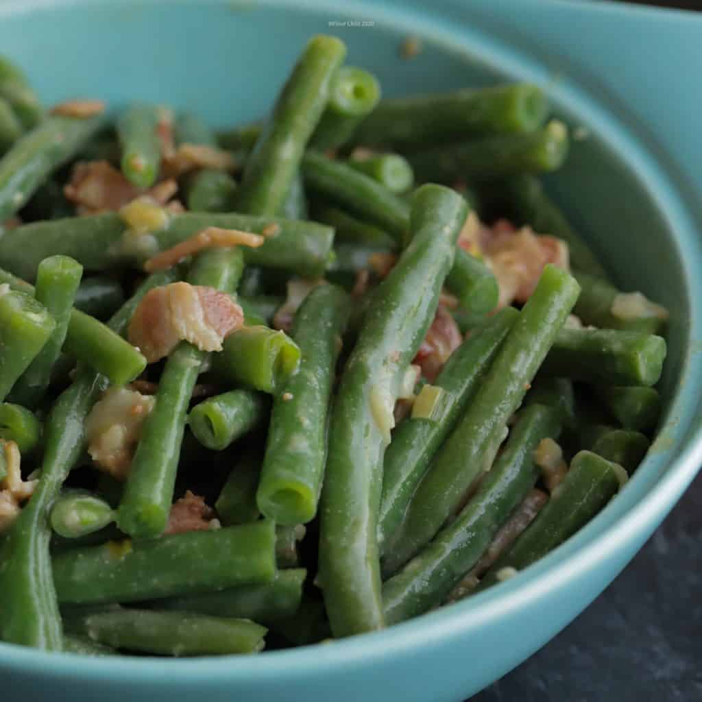 Bowl of fresh green beans dijon in a blue serving bowl