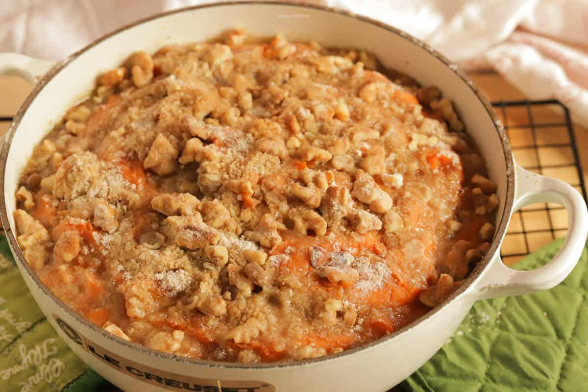 sweet potato casserole topped with pecans in a white le Creuset cast iron casserole dish