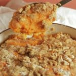 sweet potato casserole with pecan topping in a white cast iron casserole dish, with a large spoon lifting out a serving.