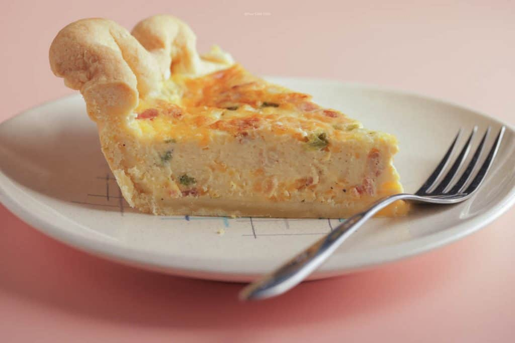 Single slice of bacon and asparagus quiche on a small plate with a fork