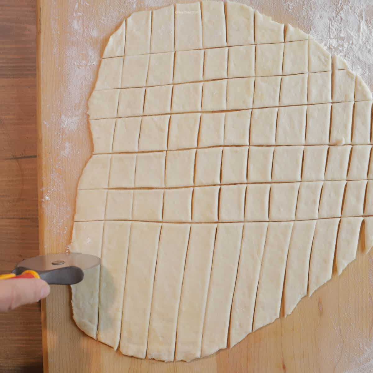Dumplings being sliced with a pizza wheel
