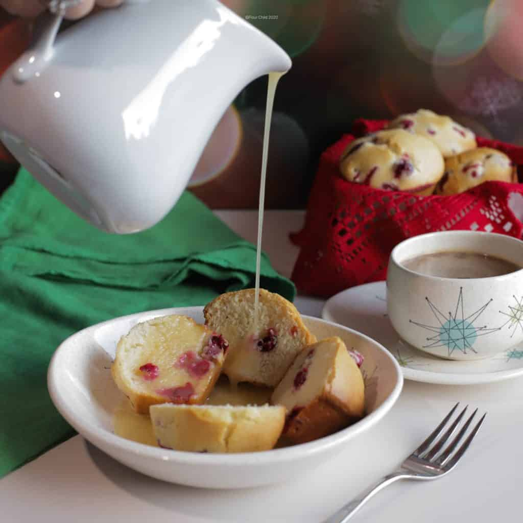 a white pitcher of butter sauce poured over a bowl of cranberry pudding