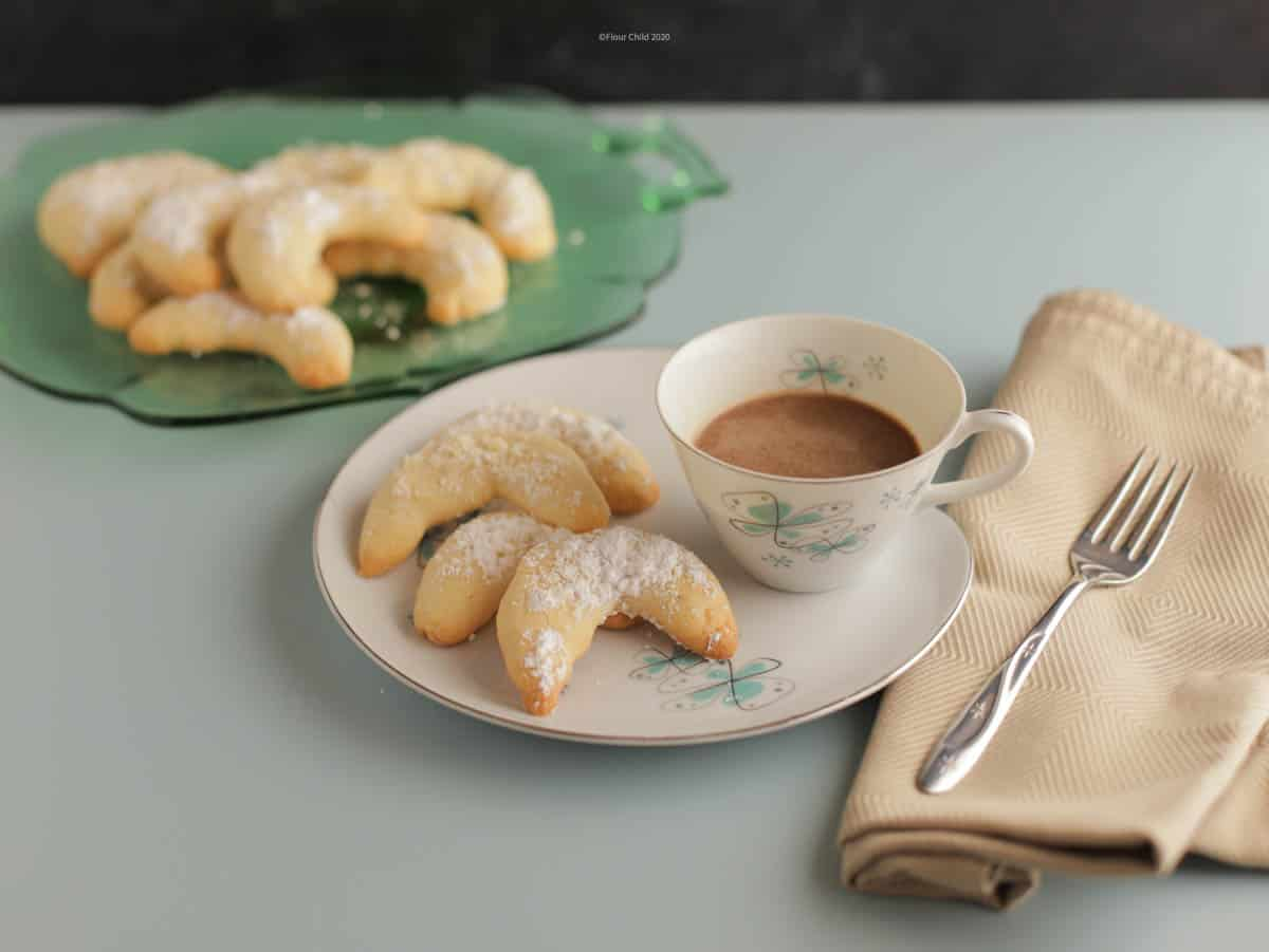 A plate with 3 crescent cookies on it next to a cup of coffee, with a serving tray of cookies in th background