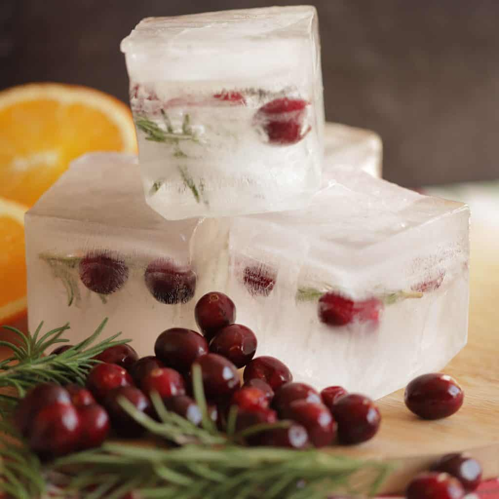 3 giant holiday ice cubes filled with cranberries and rosemary are stacked on a wooden cutting board