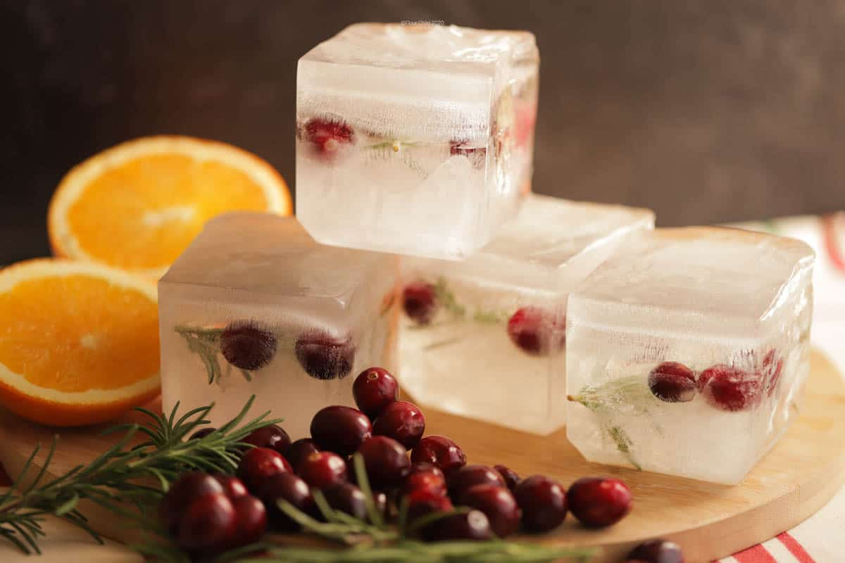 Stack of 4 giant holiday ice cubes with cranberries and rosemary inside