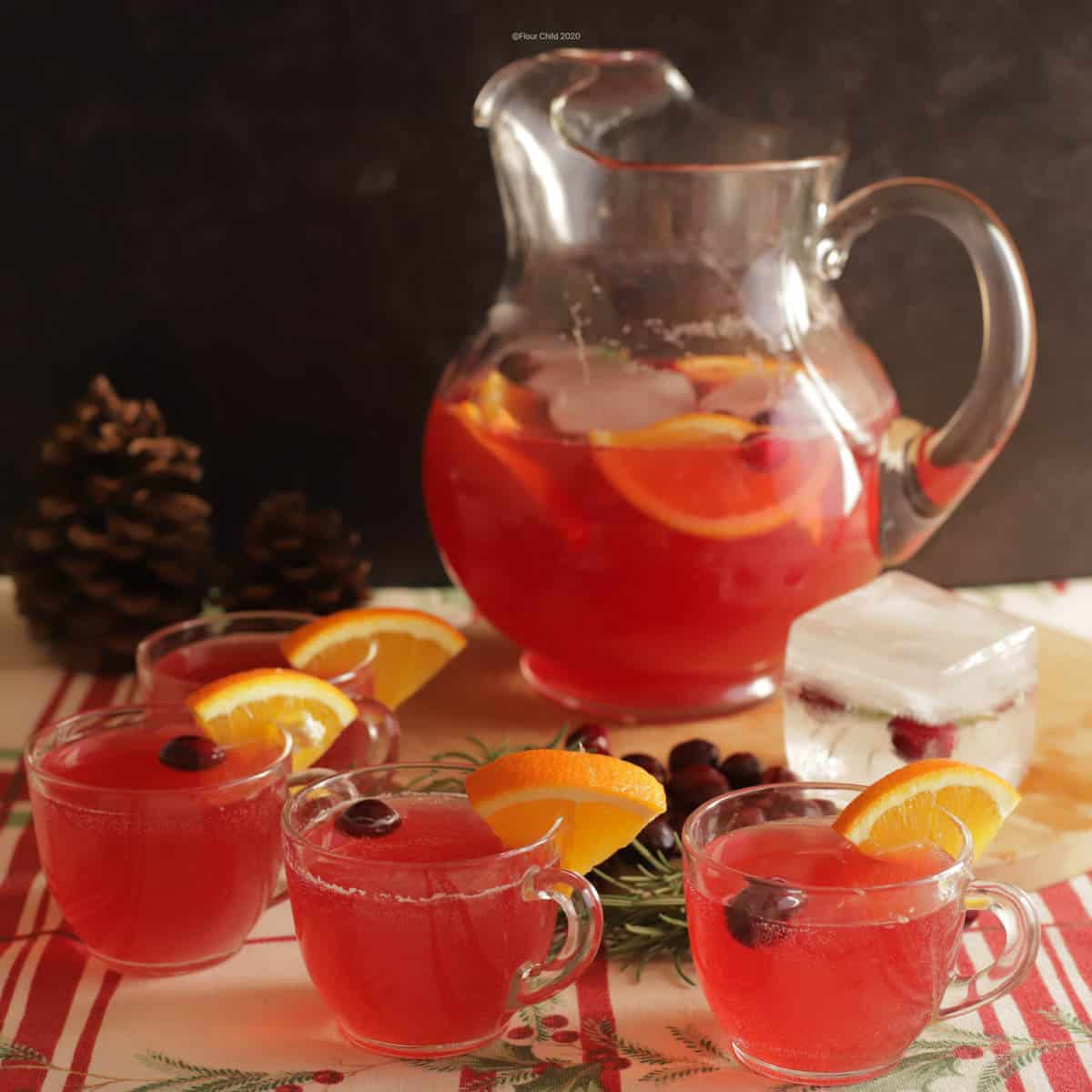 A pitcher of pink non alcoholic holiday punch with slices of orange and cranberries inside, with
