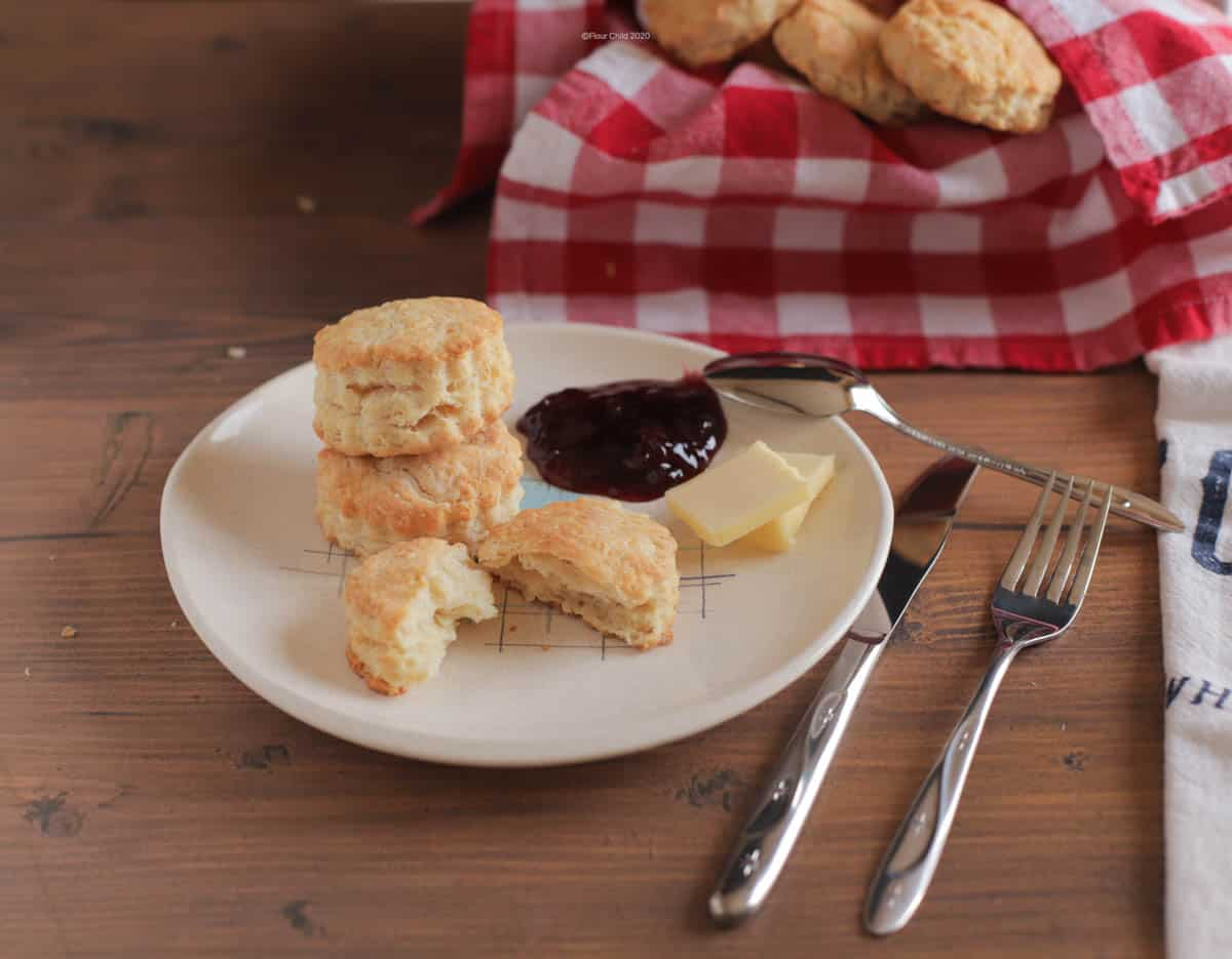 Biscuits stacked on a plate with butter and preserves