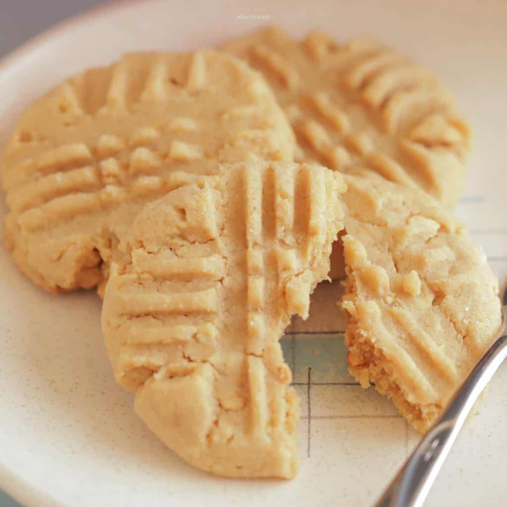 Close up image of 3 peanut butter cookies on a dessert plate